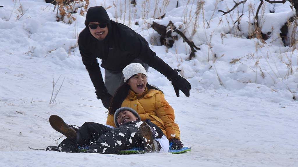 Families dressed warmly and brought plastic sleds to slide down hillsides along Sunrise Highway in the Lagunas.