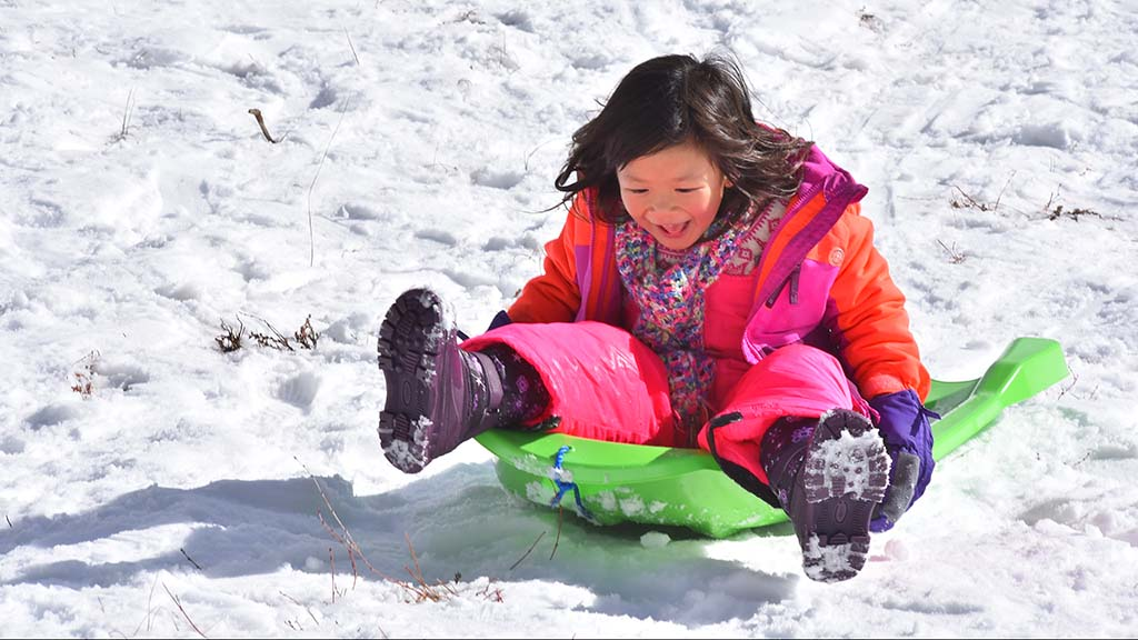 A young girl delights in her flight down a snowy slope before fresh powder arrives next week.