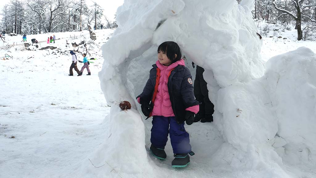 Amelia Chiu, 3, of San Diego emerges from a makeshift igloo built by families along Sunrise Highway.