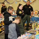 Two boys are led into Santa's Toy Workshop by county Probation elves to choose a present as part of a holiday toy and food distribution event.