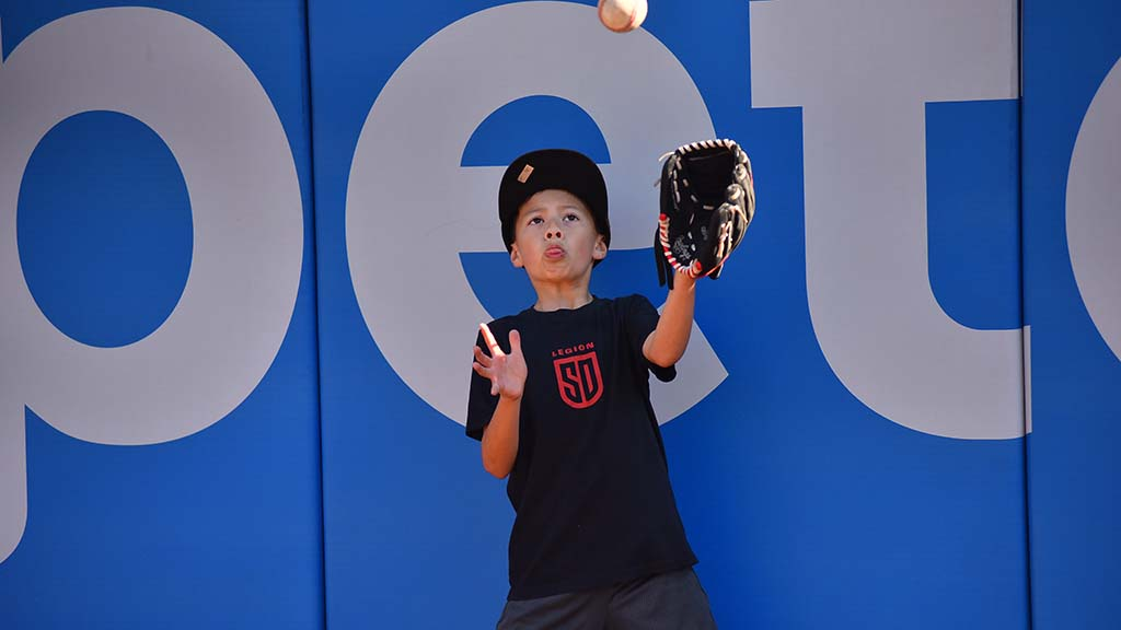 Kenneth Bleuer, 7, of San Diego practices catching a popup at the wall on the San Diego Padres field at 2020 FanFest.