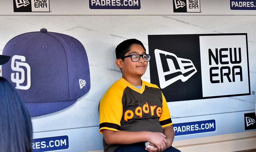 Jared Valadez, 11, smiles as he gets his photo taken in the Padre dugout at 2020 Padre FanFest.