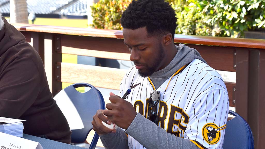 Padre prospect Taylor Trammel, an outfielder, signs a baseball for a fan.