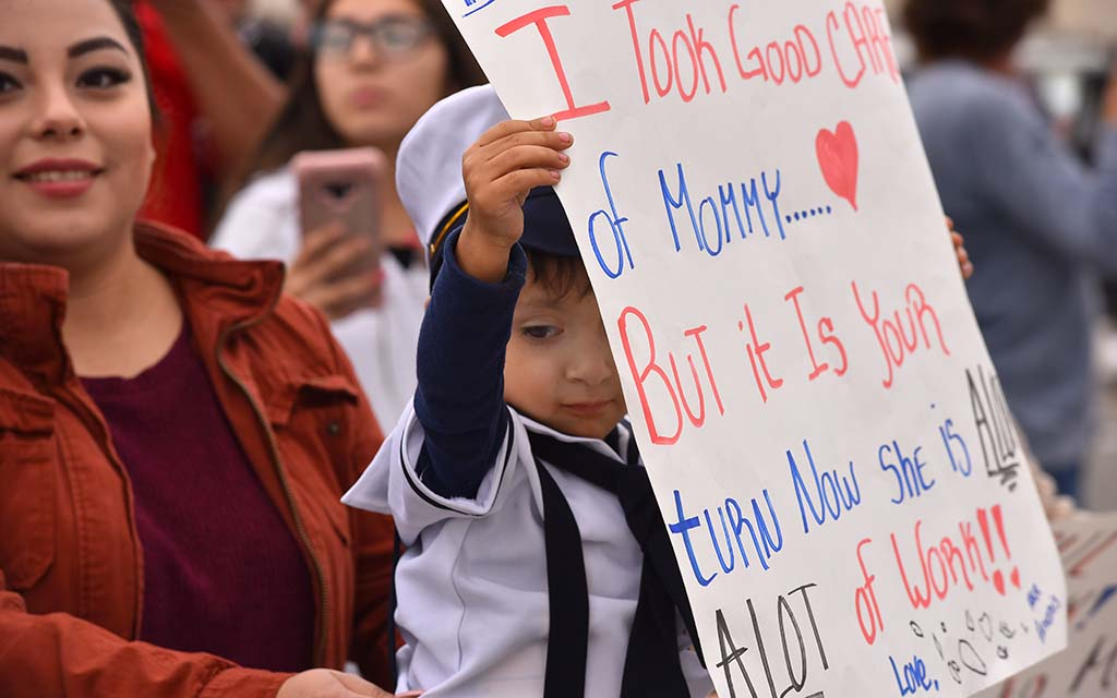 A young boy holds a sign for his father who arrived on the USS Abraham Lincoln at Naval Air Station North Island.