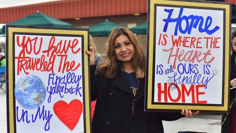 Rosa Azua holds signs for the return of her daughter, Karla Arellano, on the USS Abraham Lincoln.