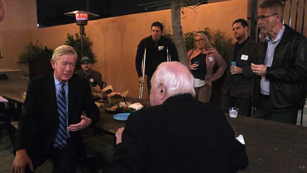 In the backyard patio of Liberty Station's Moniker General, GOP presidential candidate Bill Weld talks to Ken Blalack of La Mesa.