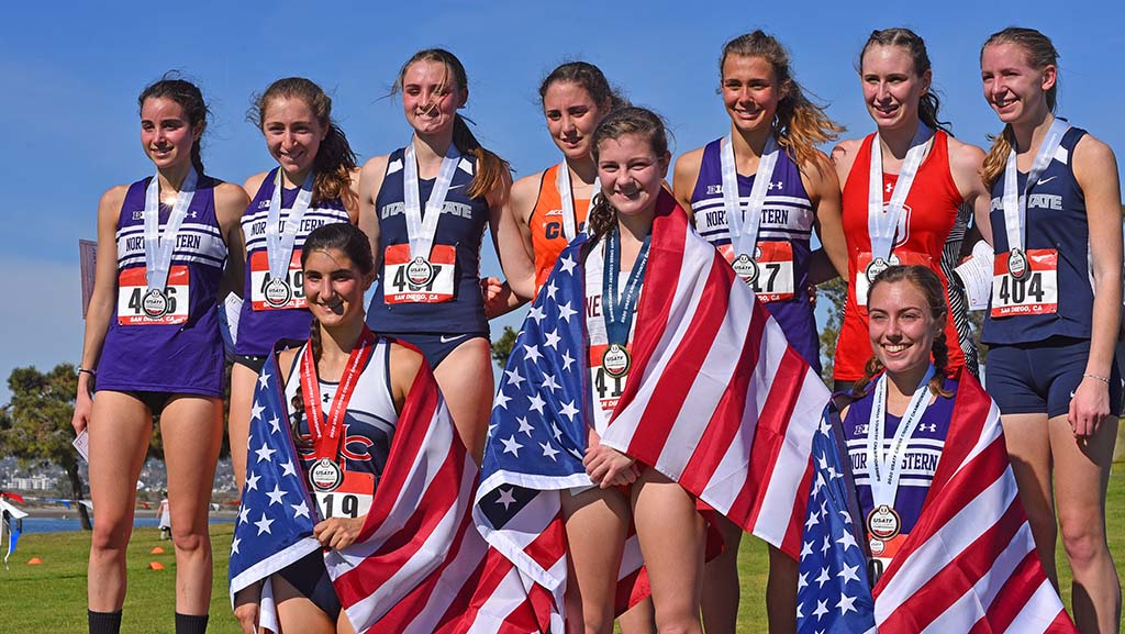 The top 10 finishers in the junior women 6k pose with their medals.