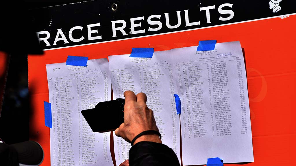 Runners check their results that were posted after each race in the USATF Cross Country Championships in Mission Bay Park.