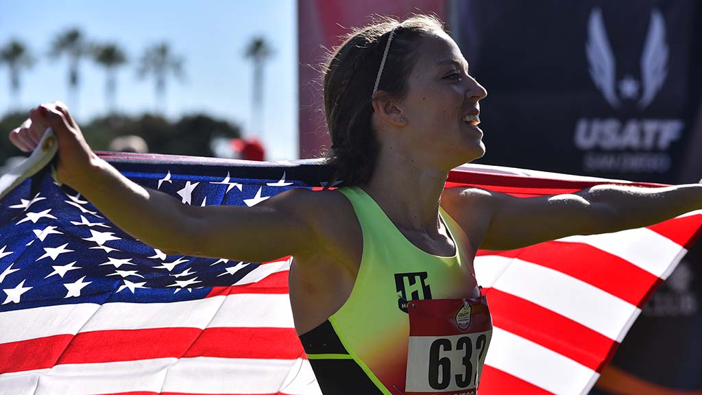 Natosha Rogers of Denver wraps herself in an American flag after winning the senior women 10k in the USATF