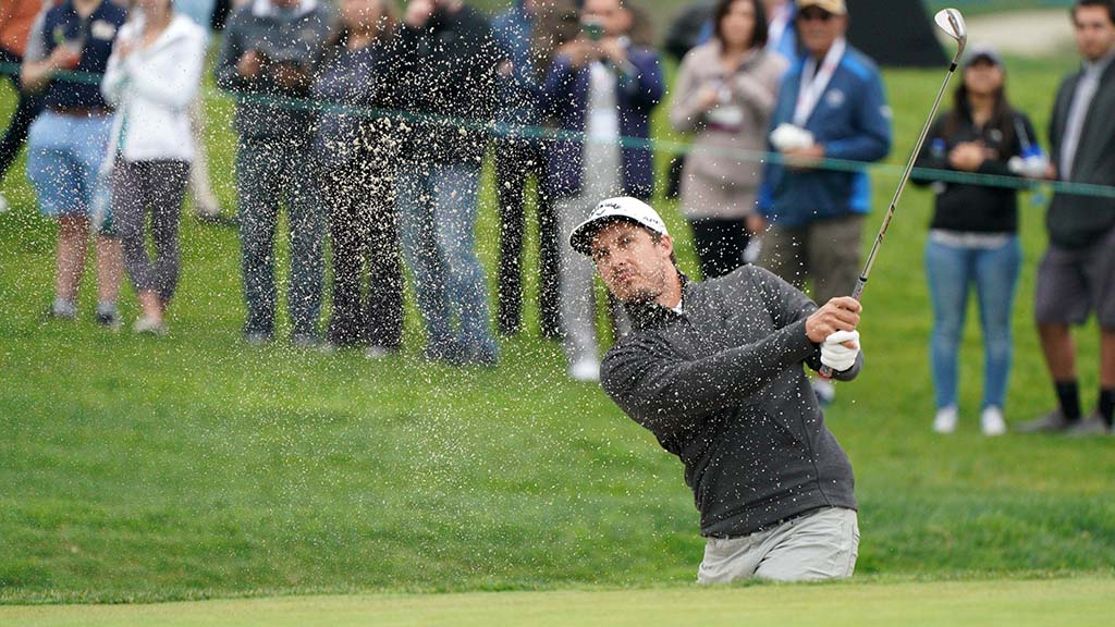 Jamie Lovemark hits out of a bunker on the 1st green of the south course of the Farmers Insurance Open.