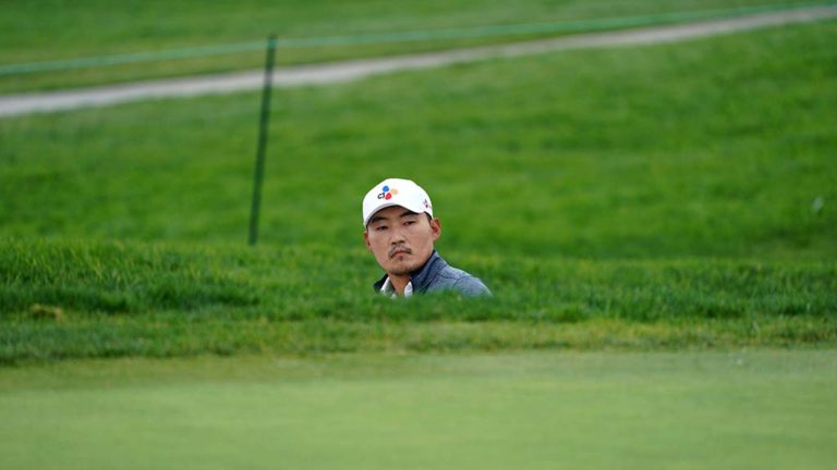 Sung Kang looks up from a bunker as he plans his next shot on the 5th green of the south course at Farmers Insurance Open.