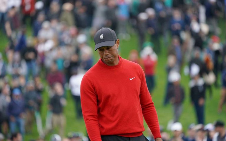 Tiger Woods reacts to a putt as fans climb hills to get a good vantage point.