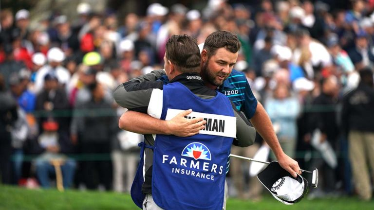 Jon Rahm, who finished in second place, hugs his caddie after completing the course.
