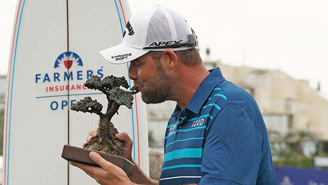 Marc Leishman of Australia kisses his winner's trophy after winning the Farmers Insurance Open with a total of 15 strokes under.