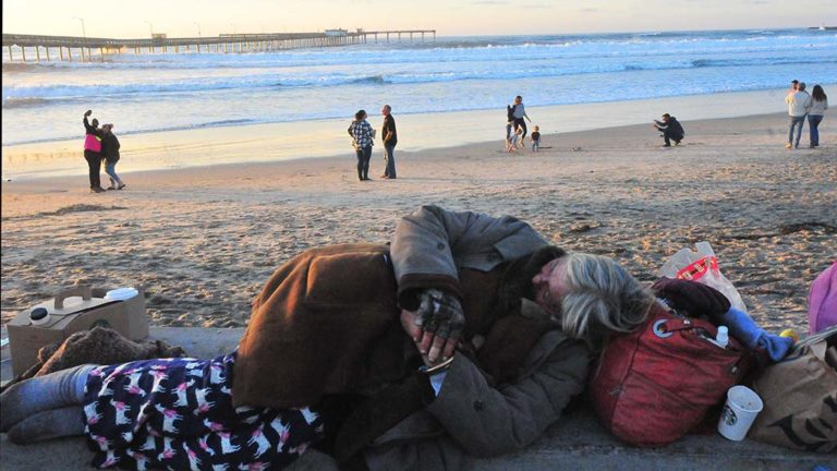 An unsheltered woman sleeps on concrete wall overlooking Ocean Beach Pier and New Year's Day visitors taking selfies.
