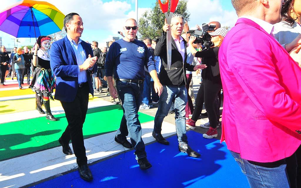 "Assemblyman Todd Gloria (left) and LGBTQ advocates make the ""catwalk"" across the rainbow crosswalk in Hillcrest."