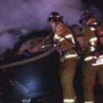 Firefighters attempt to douse burning car