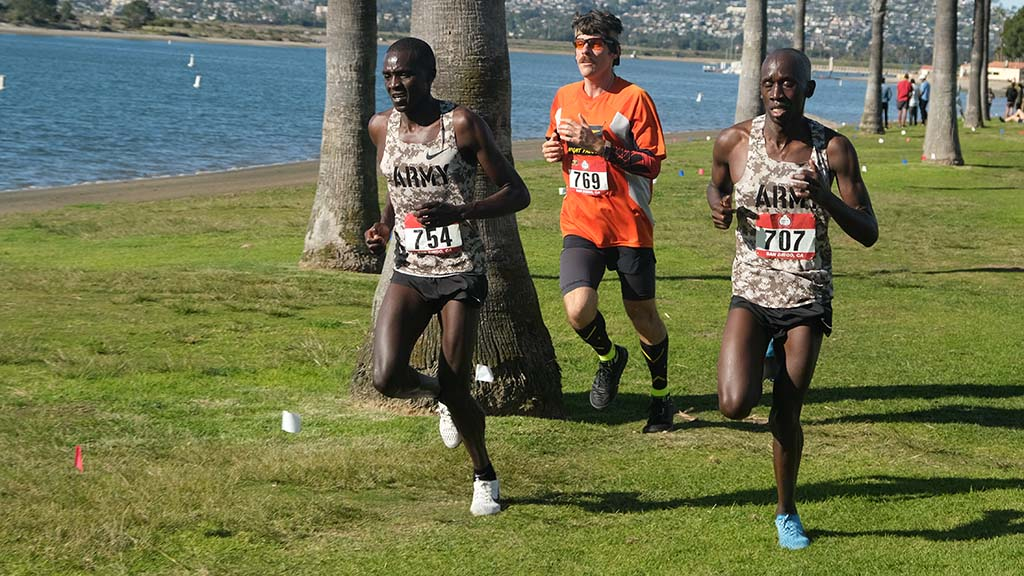 Erik Weber of San Diego, who would finish last in senior men's race, stays right as leaders Anthony Rotich and Emmanuel Bor lap him at Mission Bay Park.