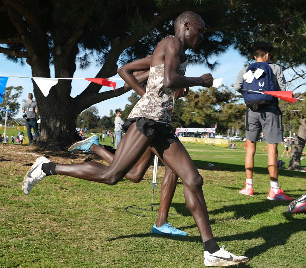 Anthony Rotich obscures Emmanuel Bor as they head down a hill stride-for-stride in Mission Bay Park.