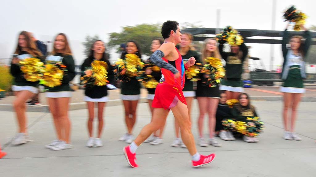 Pablo Gomez passes Patrick Henry High School cheerleaders at Olympic Trials 50K walk in Santee.