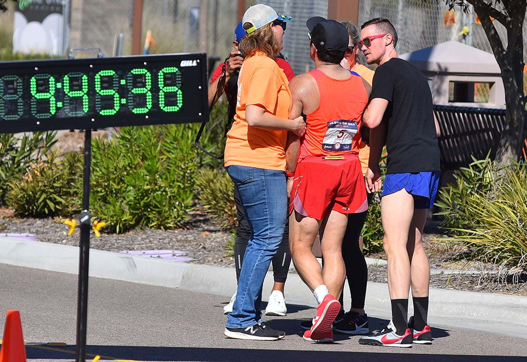 Chris Mosier (in black shirt) helped Pablo Gomez, his mentor in the sport, after nearly collapsing at the finish of 50K walk.