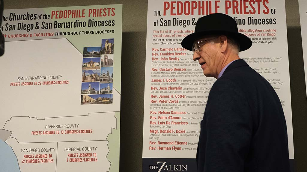 One of the unnamed plaintiffs exits past posters that name priests and show the location of the assaults.
