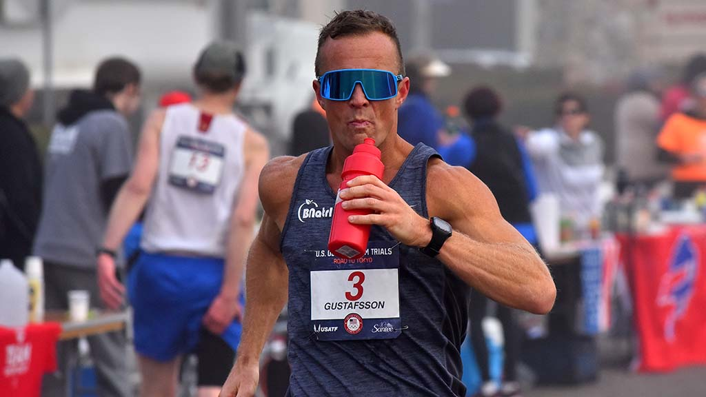 Andres Gustafsson takes a drink break in stride during the foggy portion of 50K race walk.