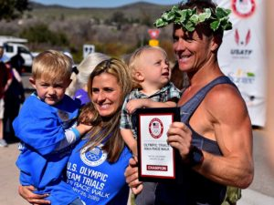Molly and Andreas Gustafsson show off his award while holding their two young sons.