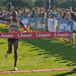Anthony Rotich of Army salutes as he wins the senior men's 10K while co-meet director flashes a USC Trojan sign in return.