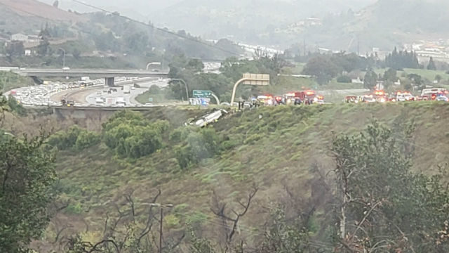 Bus on its side on the freeway embankment