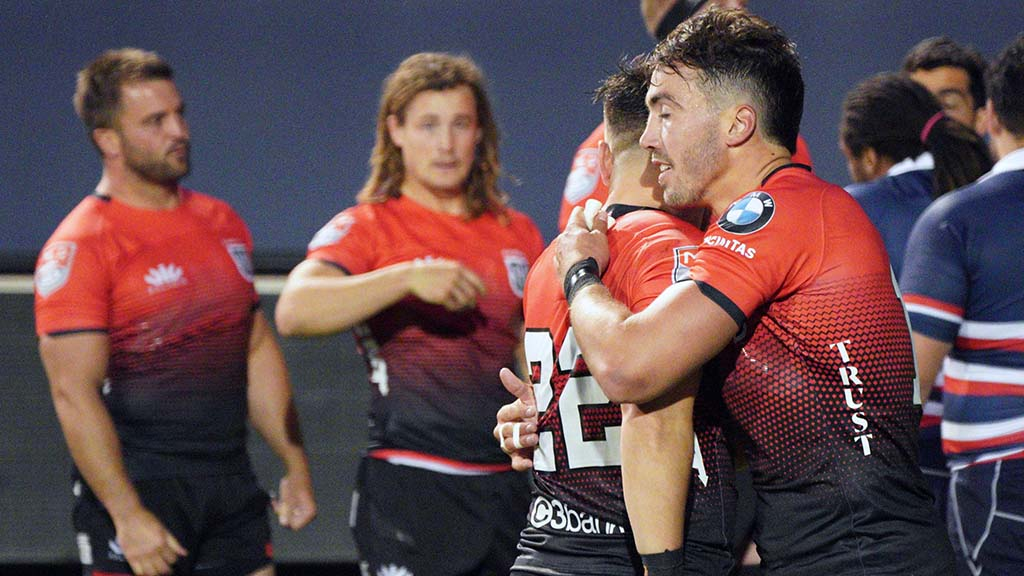 Luke Burton (right) and Devereaux Ferris, who scored a try, exchange congratulations after the match.