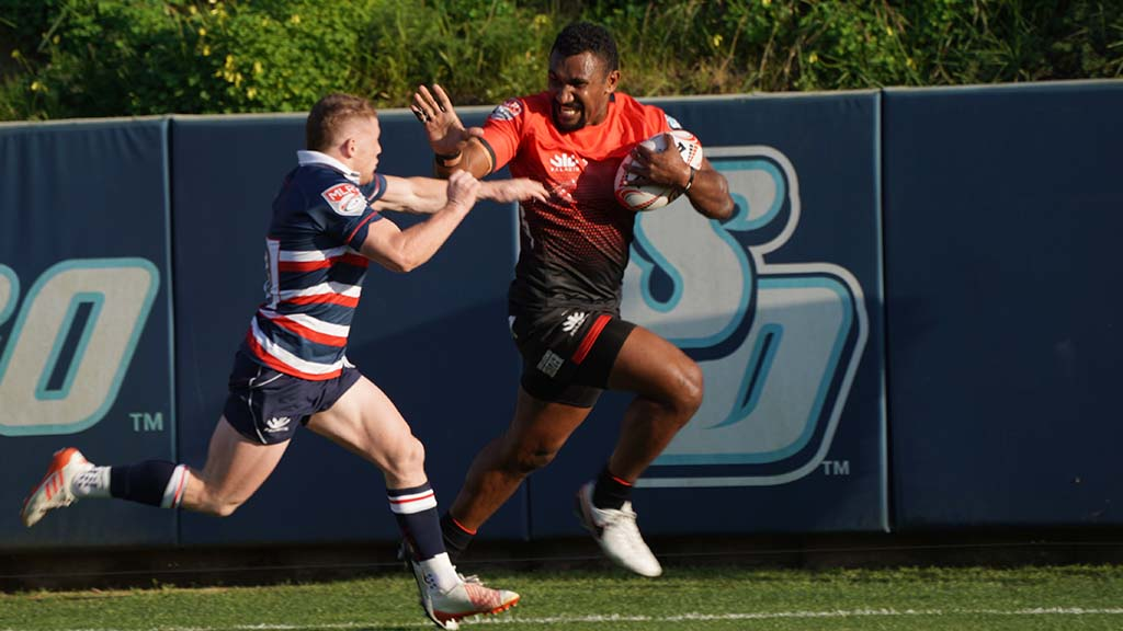 Tira Patterson powers past a New England player to score a try.