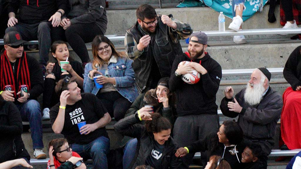 A fan catches a ball kicked in the stands and momentarily holds it.