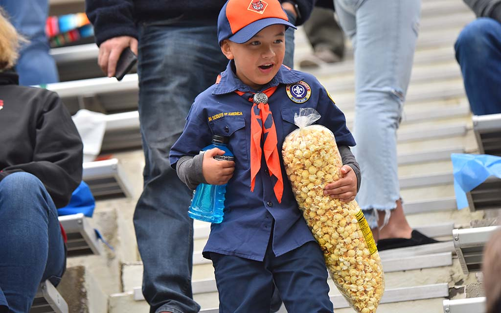 A cub scout returns to his seat after half time with a bag of popcorn almost half his height.