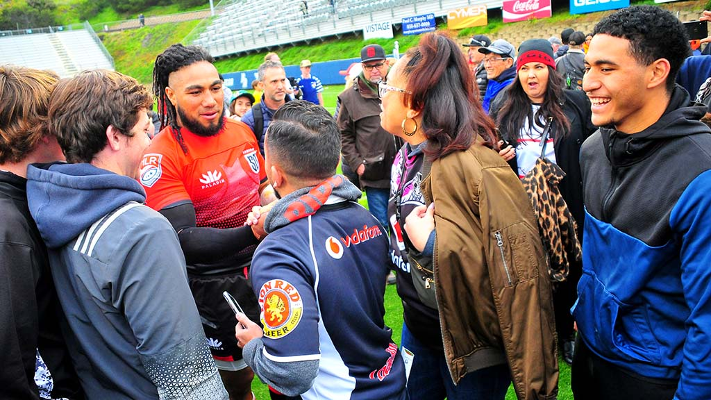 Rugby legend Ma'a Nonu of New Zealand, new to San Diego, is surrounded by fans seeking selfies and autographs after the match.
