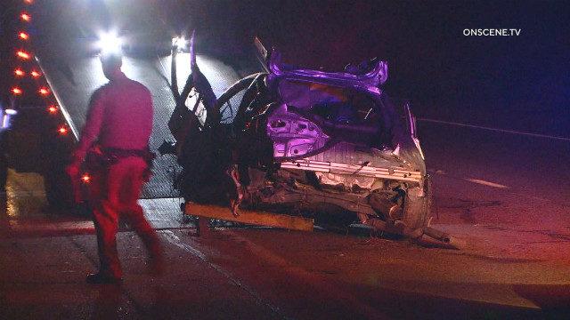 Highway Patrolman walks past wrecked car
