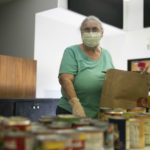 A food bank volunteer fills a bag of groceries