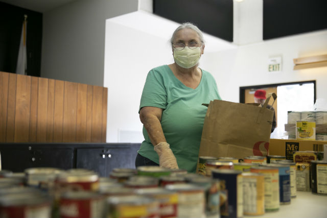 A food bank volunteer fills a bag of groceries