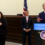 Mayor Kevin Faulconer, with sign-language interpreter and Councilman Chris Cate, tells of latest San Diego moves against the spread of coronavirus and help for local business.