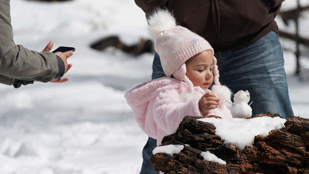 Marceys Aguirre of El Cajon makes a mini snowman on her first visit to snow.