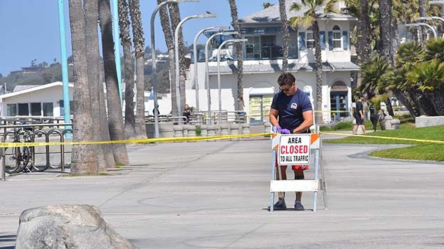 A Pacific Beach lifeguard attaches police tape to block people using the boardwalk despite the signs.