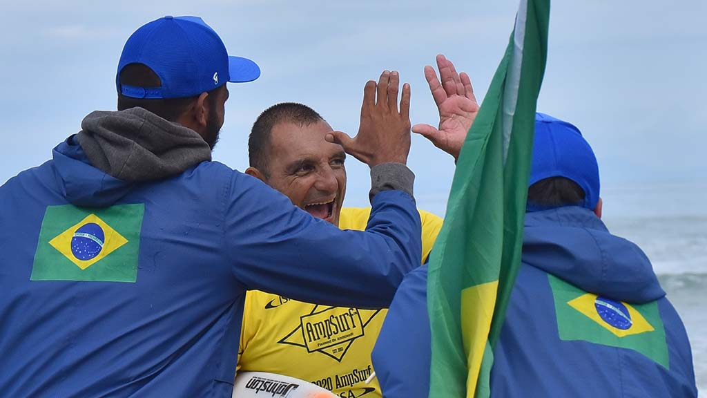 Alcino Neto from Brazil receives congratulations from compatriots after winning the kneel surfing category in the Ampsurf 2020 ISA World Para Surfing Championship on La Shores Beach.