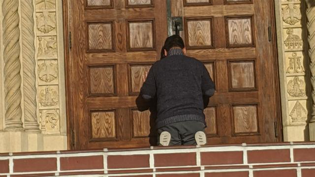 Worshiper at closed doors of St. Joseph Cathedral