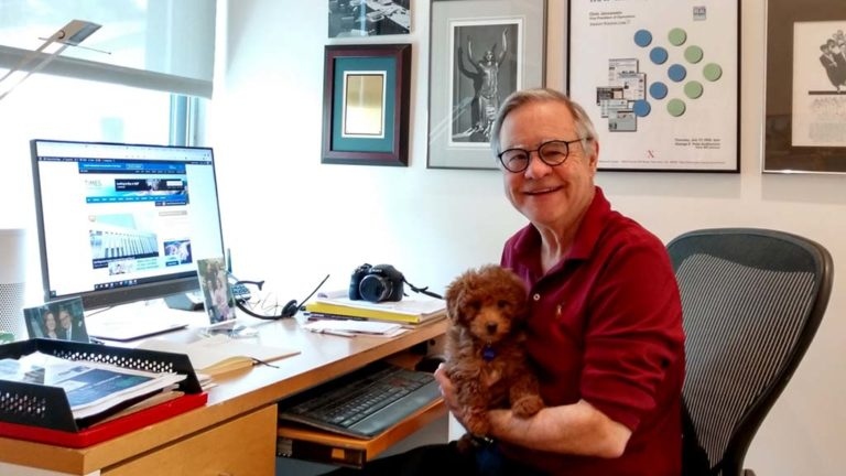 Times of San Diego editor and publisher Chris Jennewein at his home office holds Razzleberry, the family's new Miniature Goldendoodle puppy.