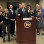 San Diego Mayor Kevin Faulconer speaks at county press conference on Covid-19 response, with mayor officials arrayed behind him.