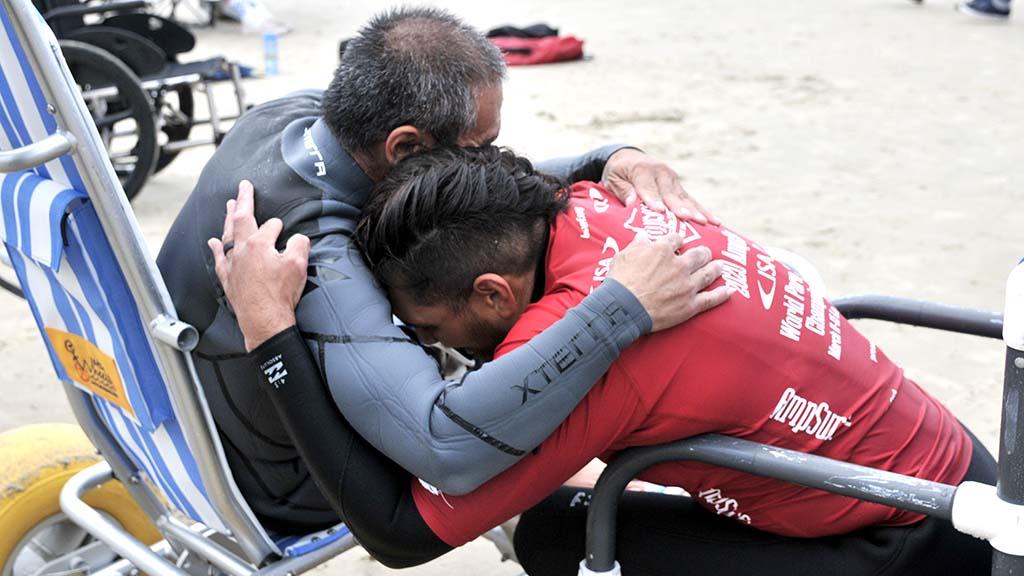 Jose Martinez of California and Buster Kawasaki from Hawaii embrace after finishing their semifinal heat at the Ampsurf 2020 ISA World Para Surfing Championship at La Shores.