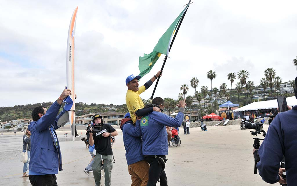 Alcino Neto from Brazil is carried by compatriots after winning the kneel surfing category in the Ampsurf 2020 ISA World Para Surfing Championship at La Shores.