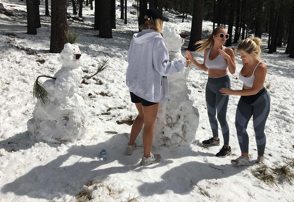 Three UC Santa Barbara students staying with a Mission Beach family added their own touches to a Laguna Mountains snowman.