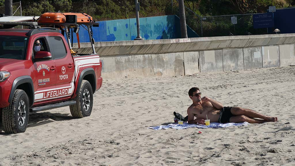 A man who was relaxing on a blanket near the Ocean Beach Pier was told by a lifeguard that rules bar lying on the beach.