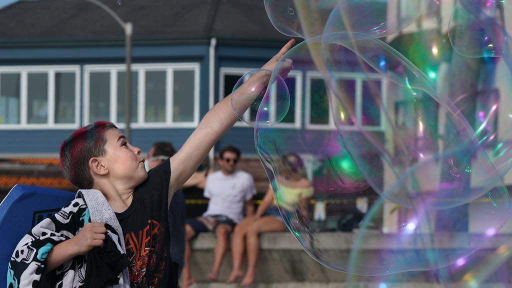A young boy plays with bubbles made by Alan James at Ocean Beach Pier.